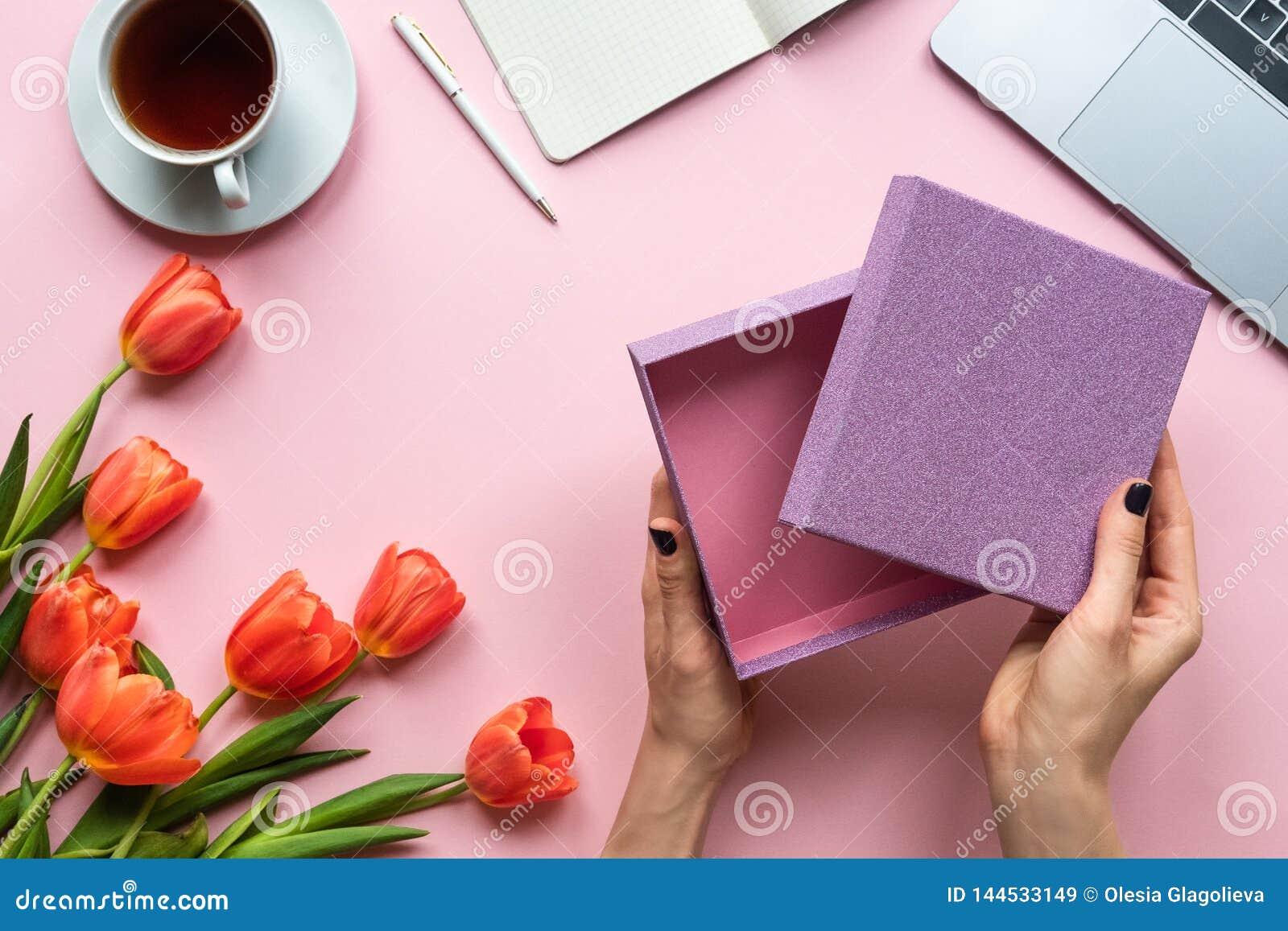 Mani femminili con la scatola vuota aperta su fondo rosa Fondo con tè, il computer portatile ed i fiori
