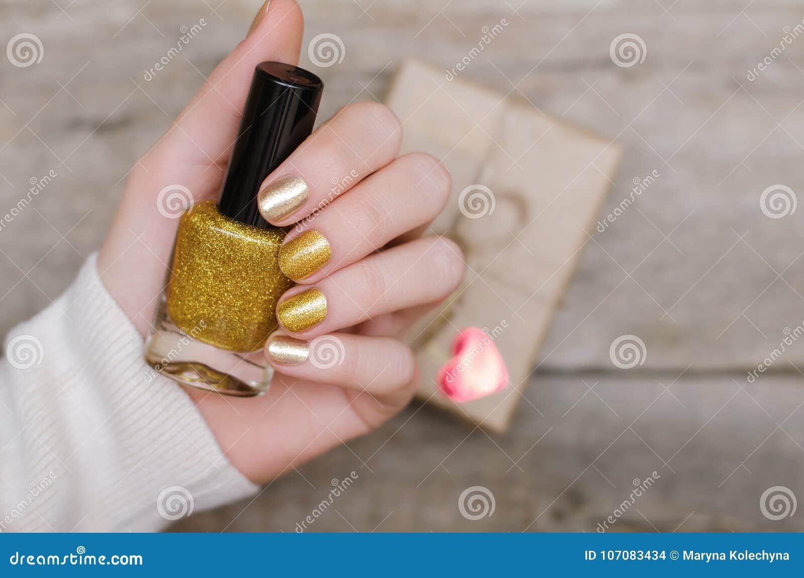 Mani femminili con progettazione del chiodo dell oro