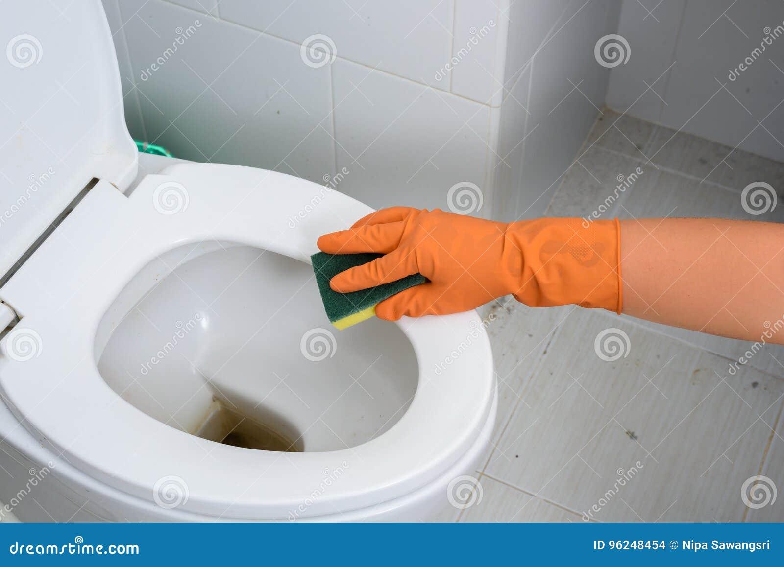 Mani in guanti arancio che puliscono WC, toilette, lavabo