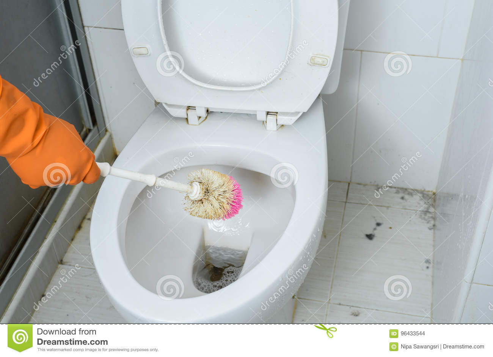 Mani in guanti arancio che puliscono WC, toilette, lavabo facendo uso della spazzola