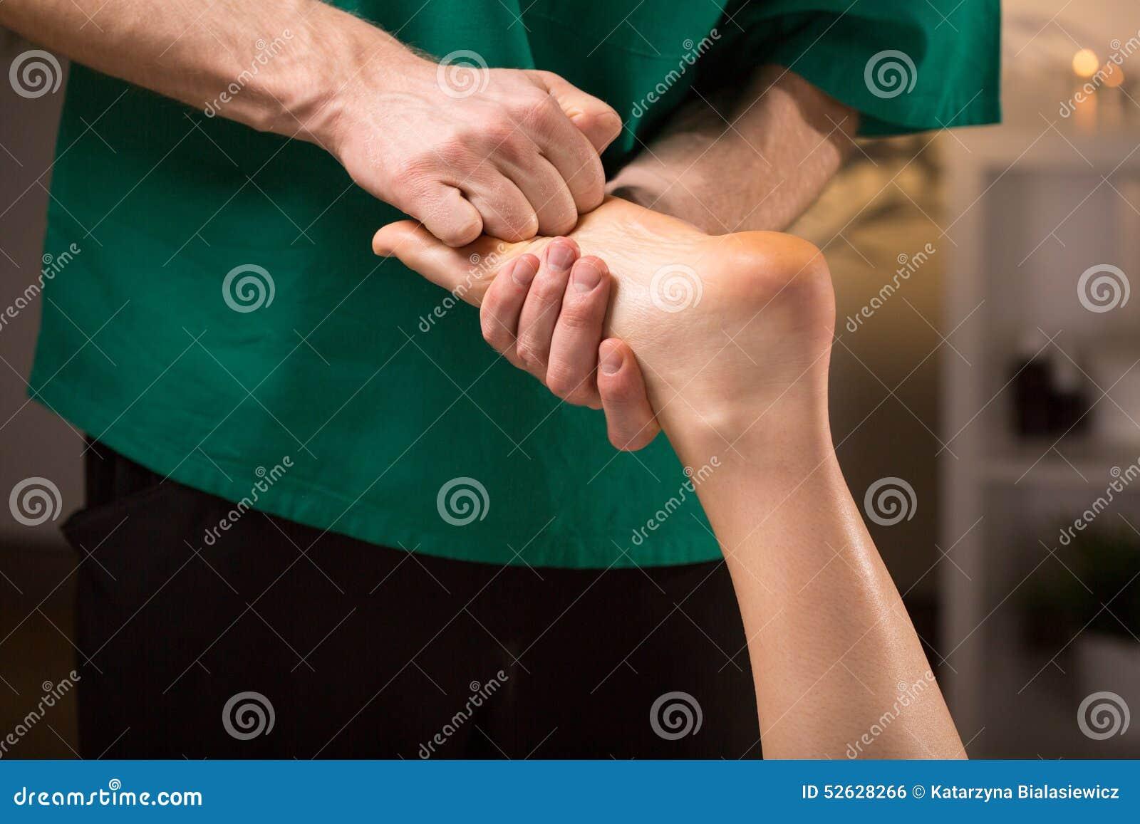 Mani maschii che fanno massaggio del piede