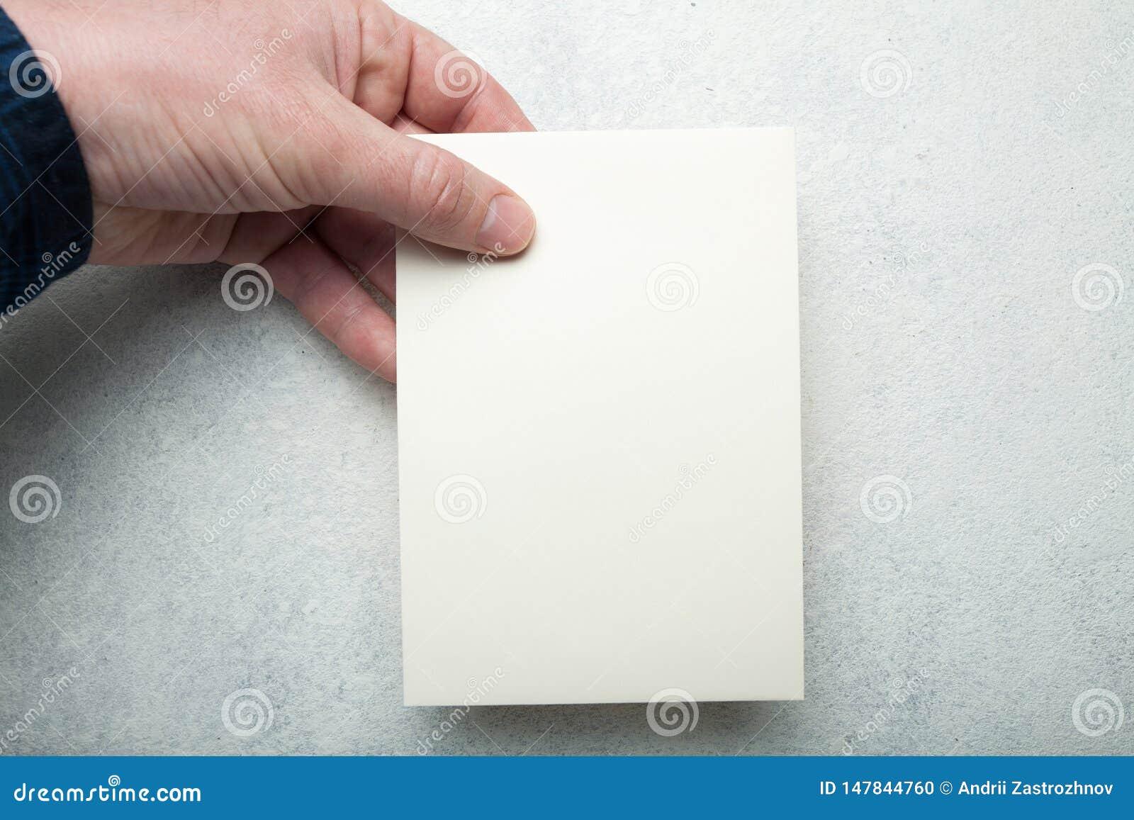 Mani maschii che tengono un aletta di filatoio in bianco su un fondo bianco d annata Aletta di filatoio, modello dell invito