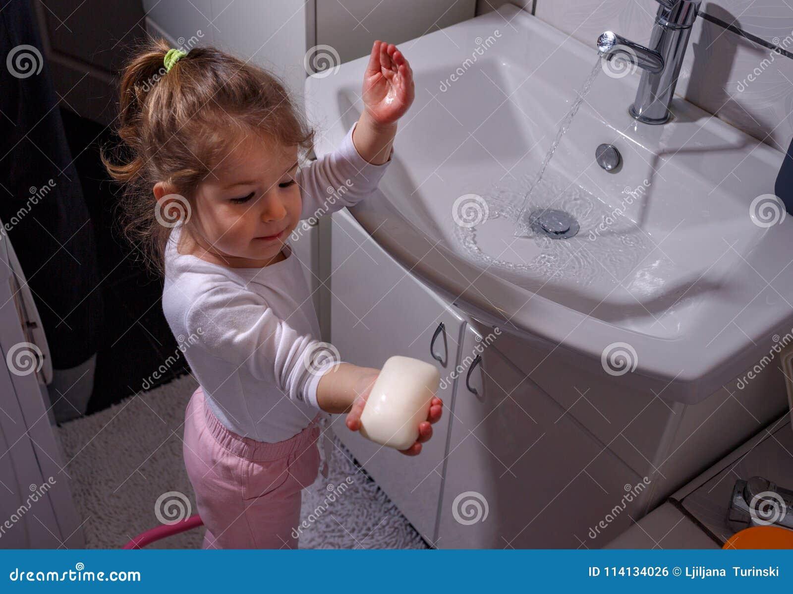 Mani sorridenti di lavaggio della bambina in bagno