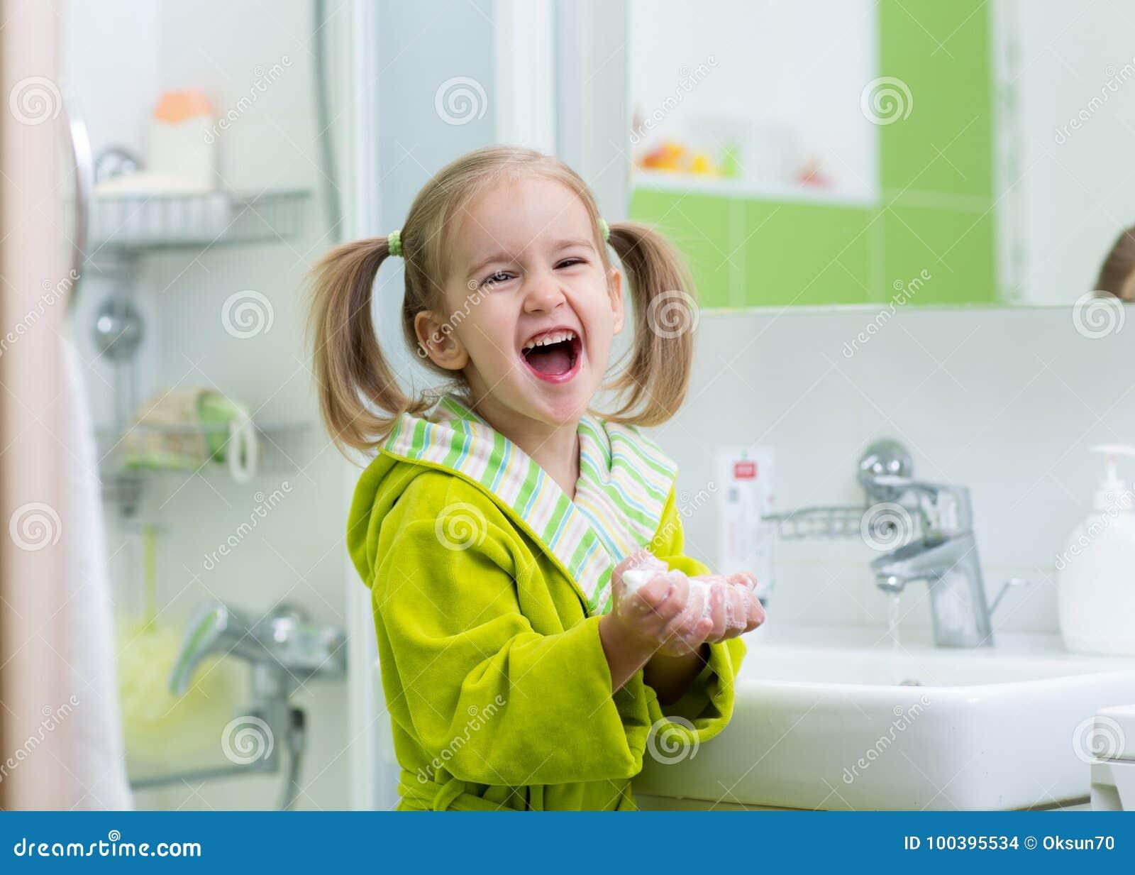 Mani sorridenti di lavaggio della bambina del bambino in bagno