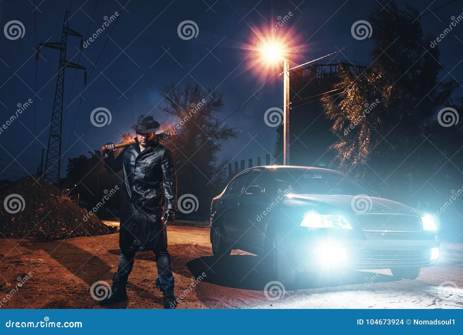 Maniac with bloody baseball bat against black car