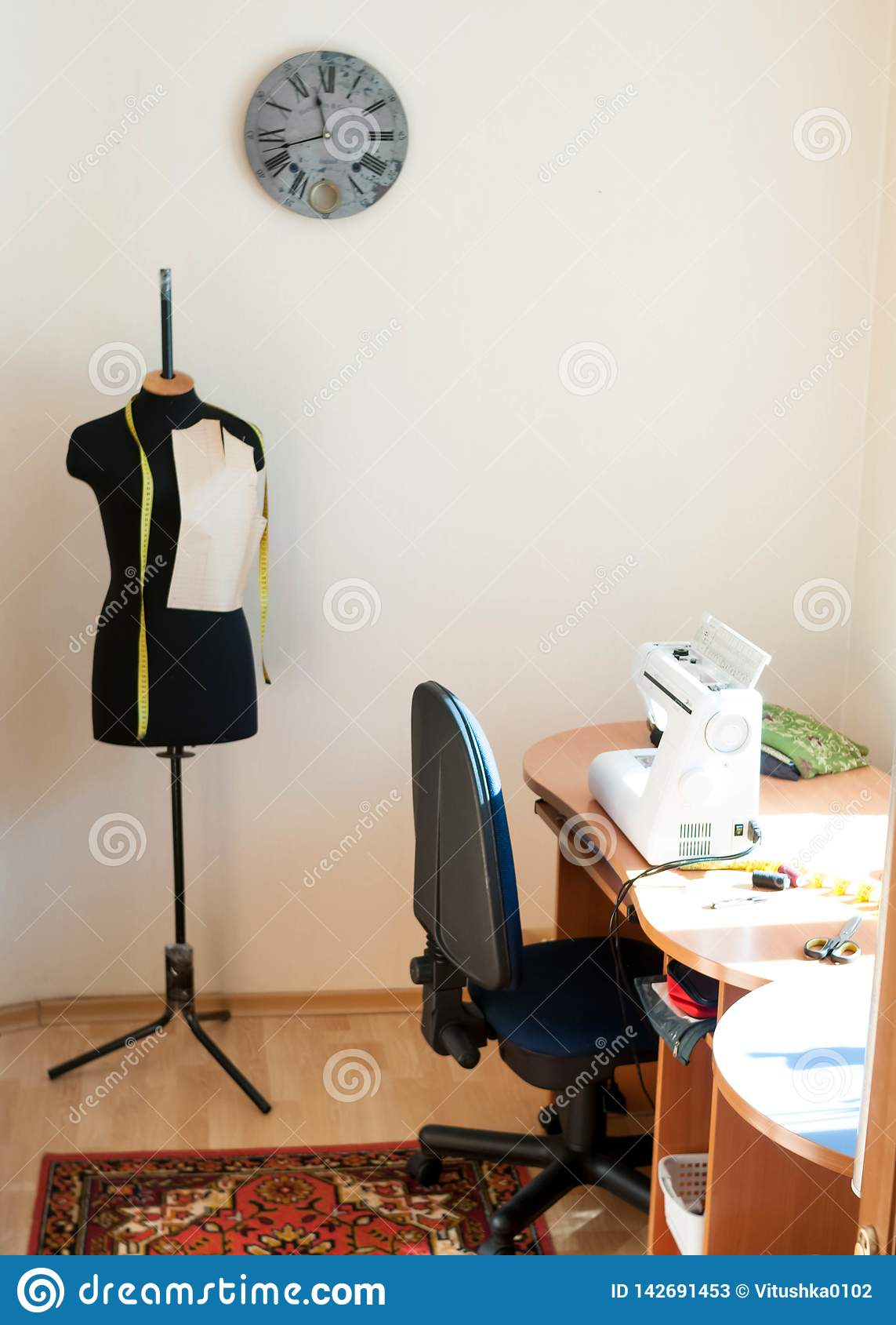 Manichino e tavola di legno con la macchina per cucire
