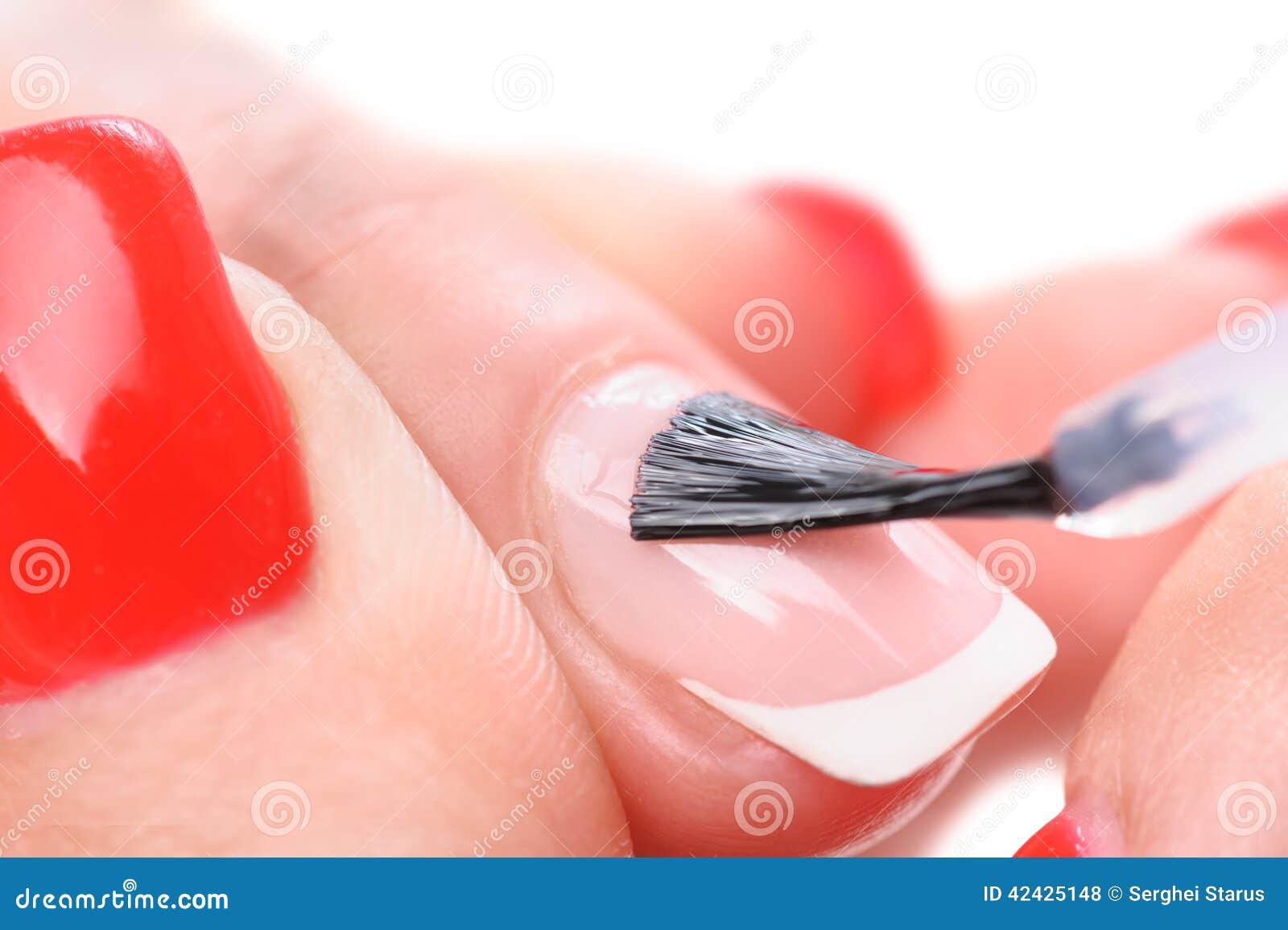 Manicura, aplicando el esmalte claro