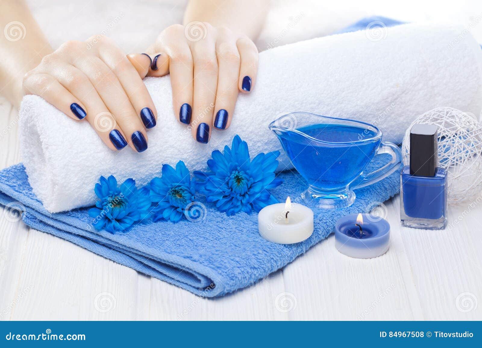 Manicura azul hermosa con el crisantemo y toalla en la tabla de madera blanca Spa
