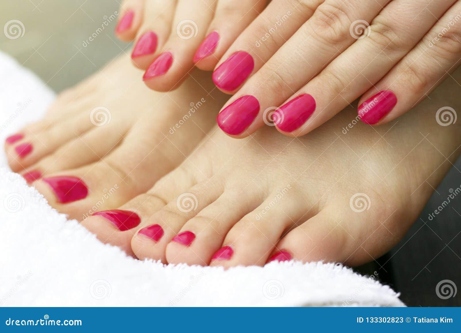 Manicura y pedicura rosadas en las manos y las piernas femeninas, primer, vista lateral