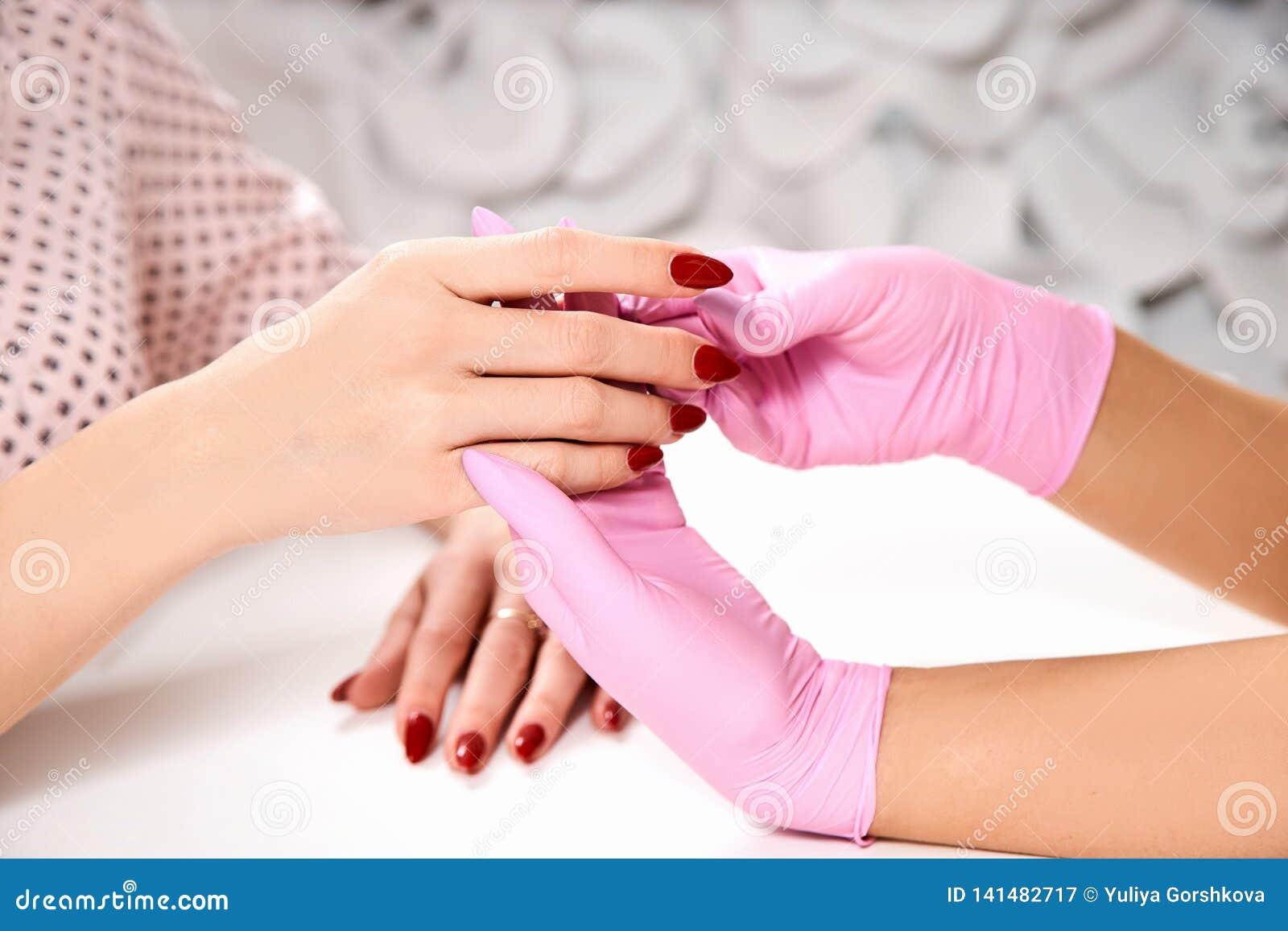 Manicure bij de schoonheidssalon De meester houdt client& x27; s overhandigt handenclose-up Roze handschoenen, rood nagellak