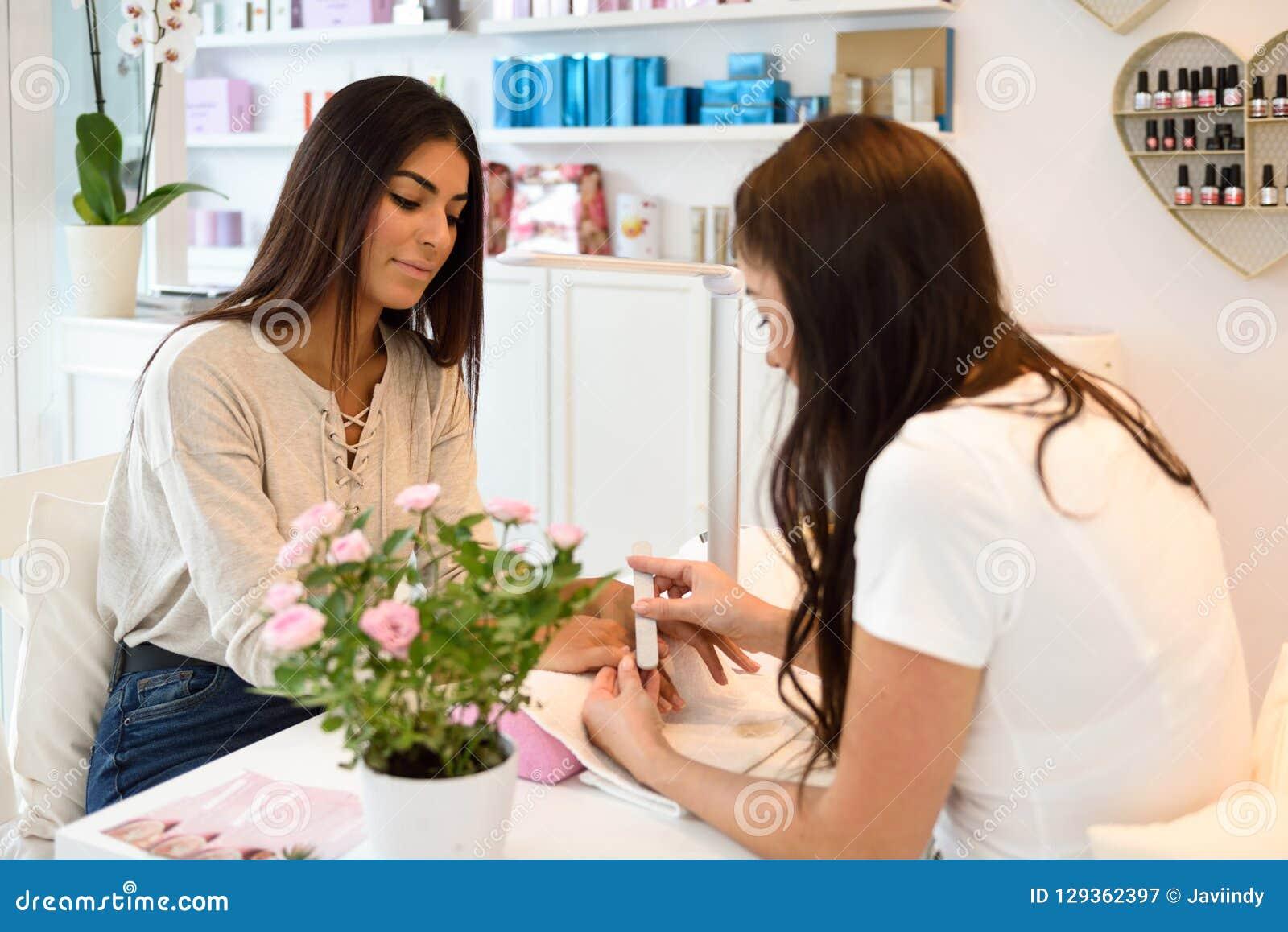 Manicure el cuidado del clavo para el cliente que se sienta en una tabla en el offi
