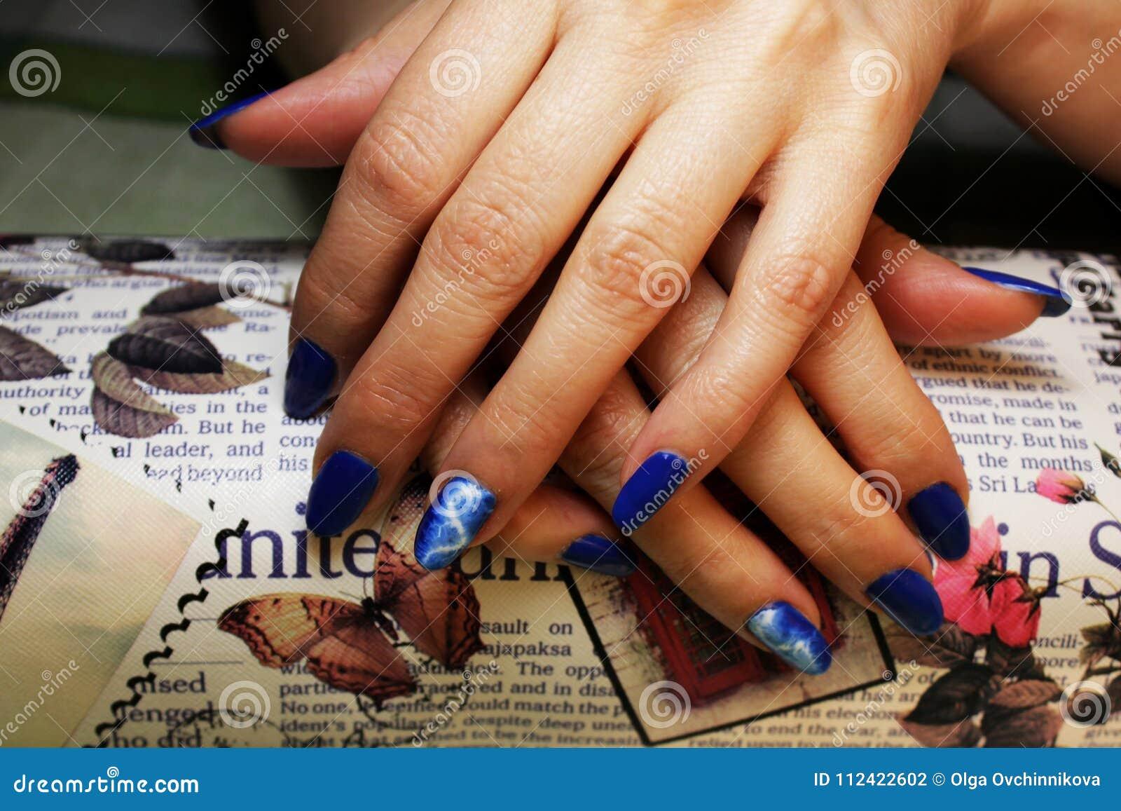 Manicure eseguito dallo studente le mani si trova sopra su un cuscino di lavoro speciale sotto forma di barra Rivestimento blu co