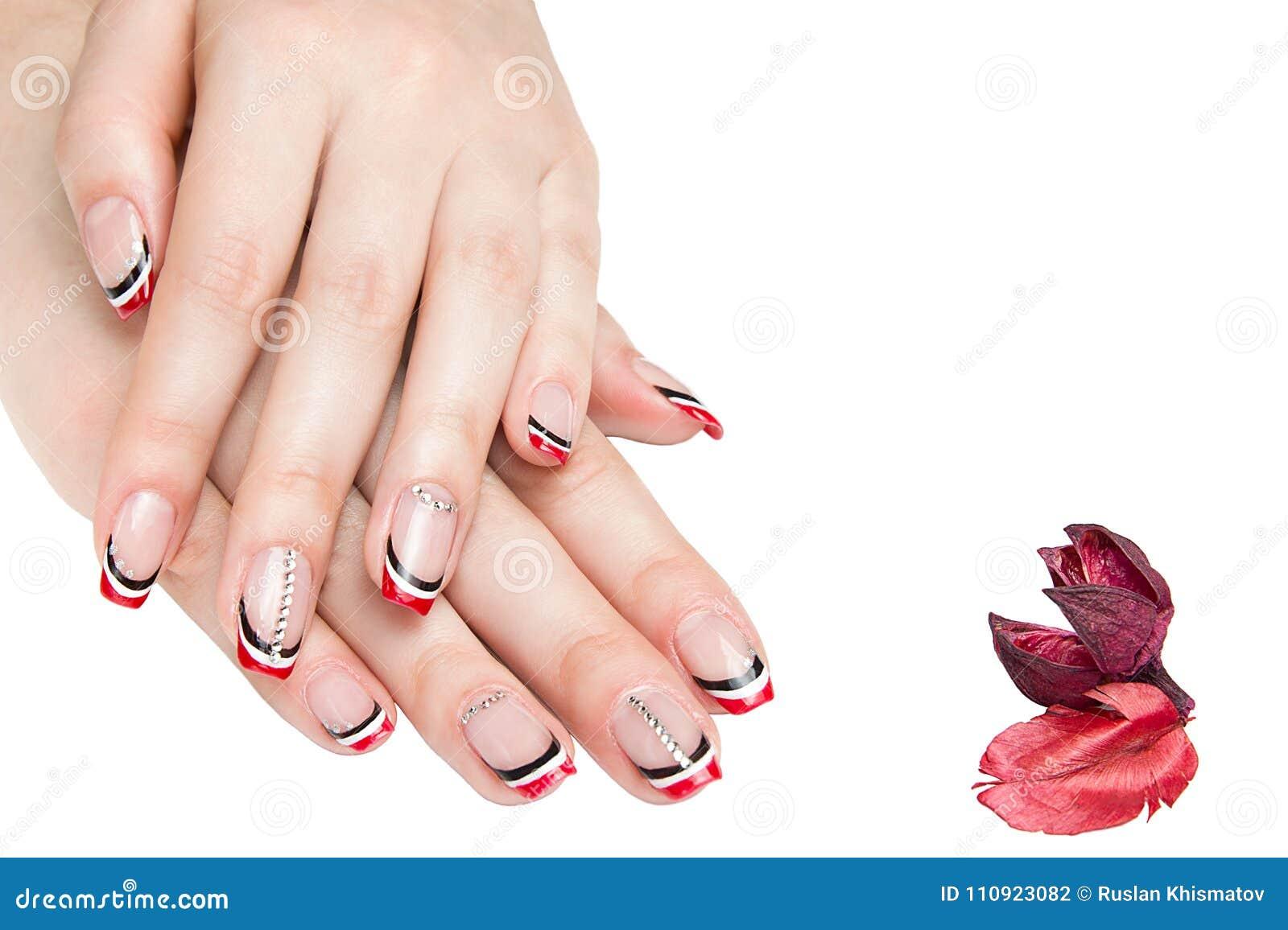 Manicure francese - belle mani femminili manicured con il manicure in bianco e nero rosso con i cristalli di rocca isolati su fon