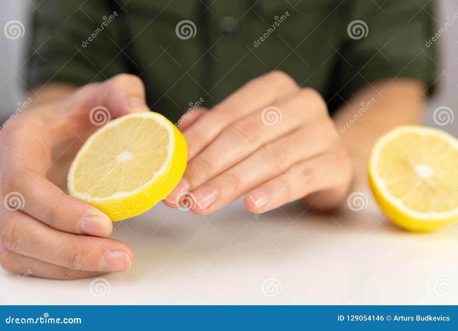 Manicure, mujer limpia sus clavos con el limón