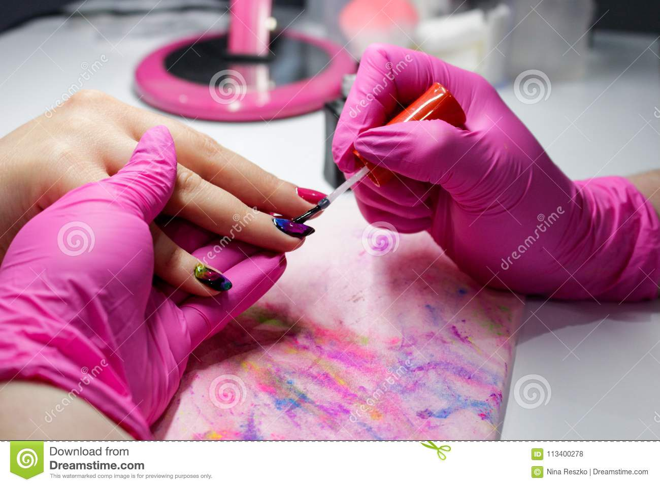 Manicure nail paint, Closeup shot of a woman in a nail salon receiving a manicure by a beautician
