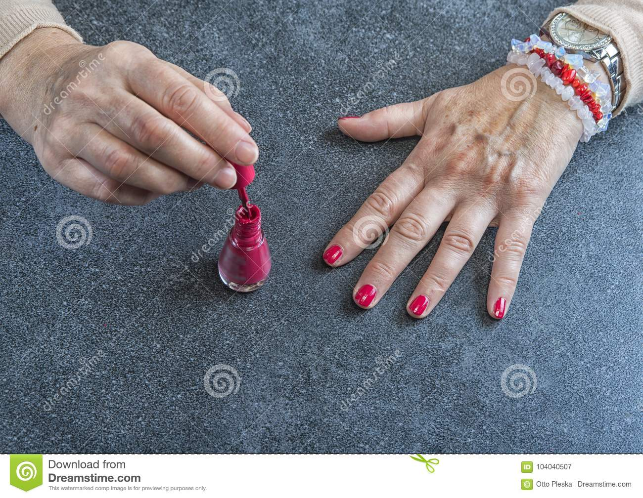 Manicure. Old Woman Hands Polishing Nails With Red Nail Polish In ...