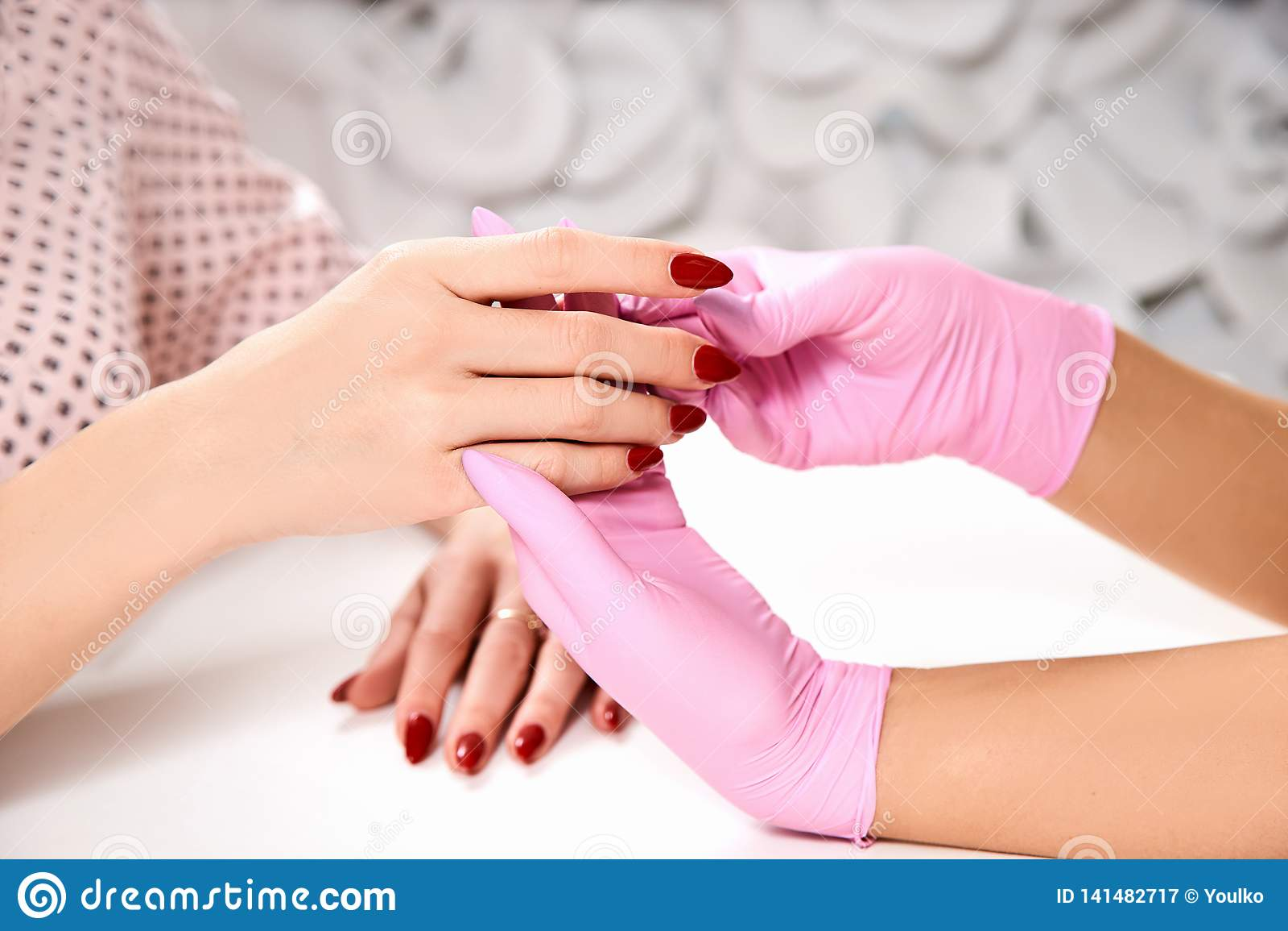 Manicure przy piękno salonem Mistrz trzyma client& x27; s ręk ręki w górę Różowe rękawiczki, czerwony gwoździa połysk