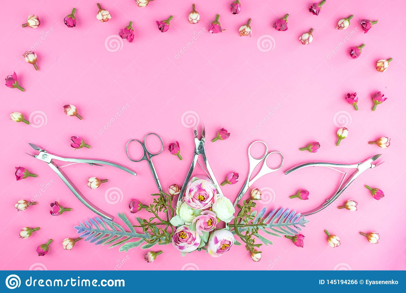 Manicure tools on a pink background decorated with flowers.