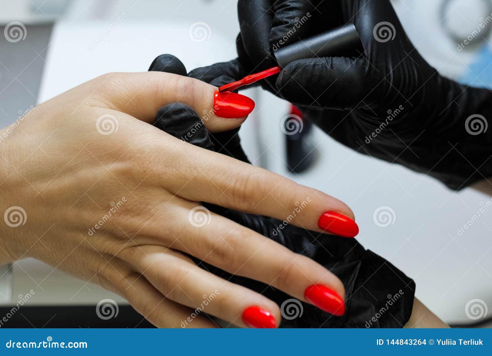 Manicure u specjalista w czarnych r?kawiczkach dba o r?ka gwo?dziach Manicurzysta farb gwo?dzie z czerwonym gwo?dzia po?yskiem