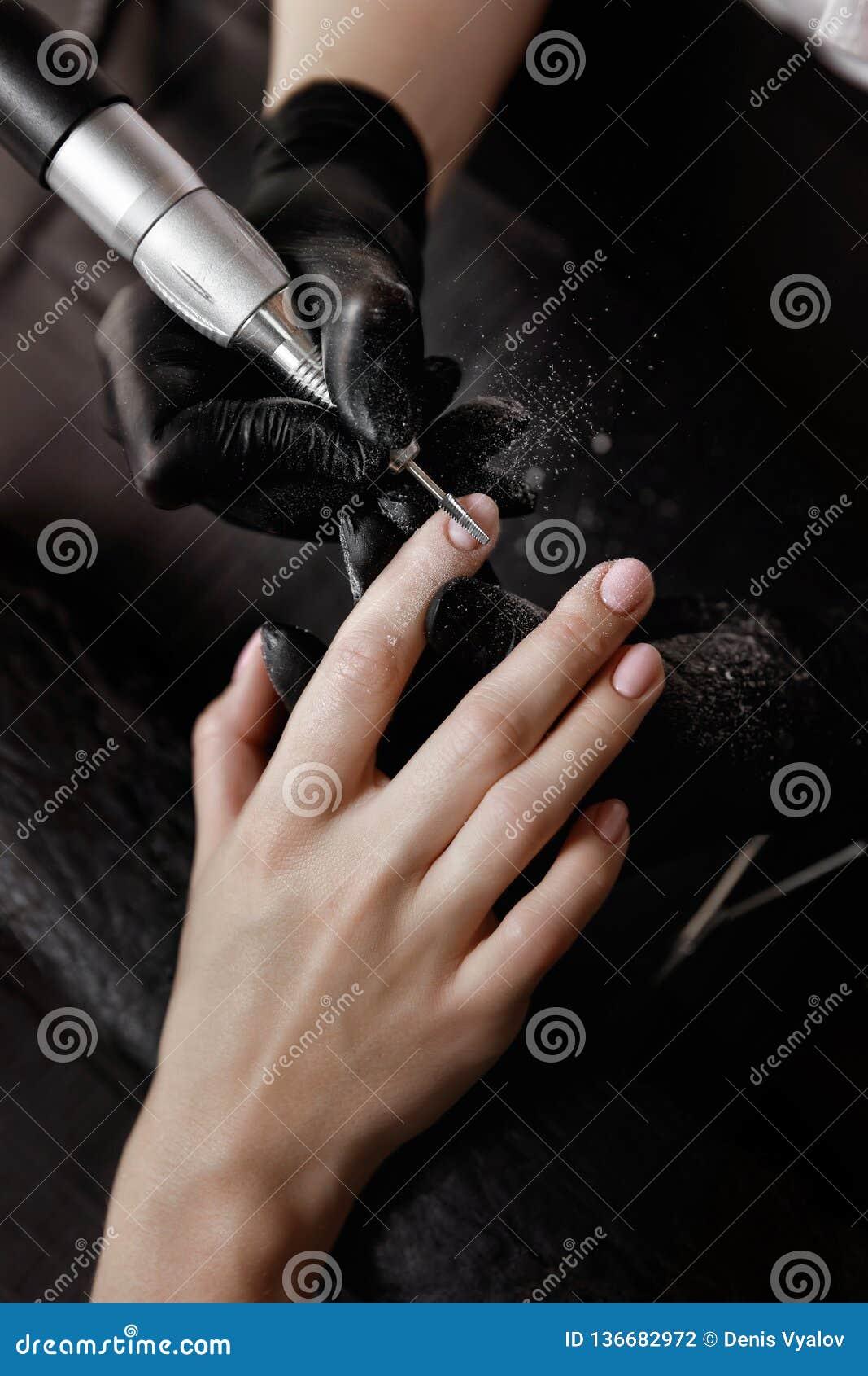 Manicurist в черных перчатках, шлифовальный станок извлекает старый блеск геля