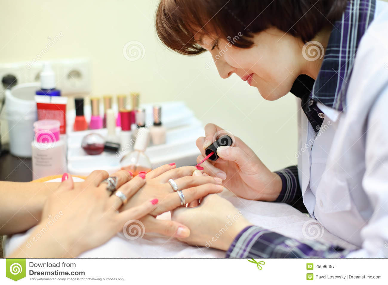 manicurist makes manicure for woman by nail polish royalty