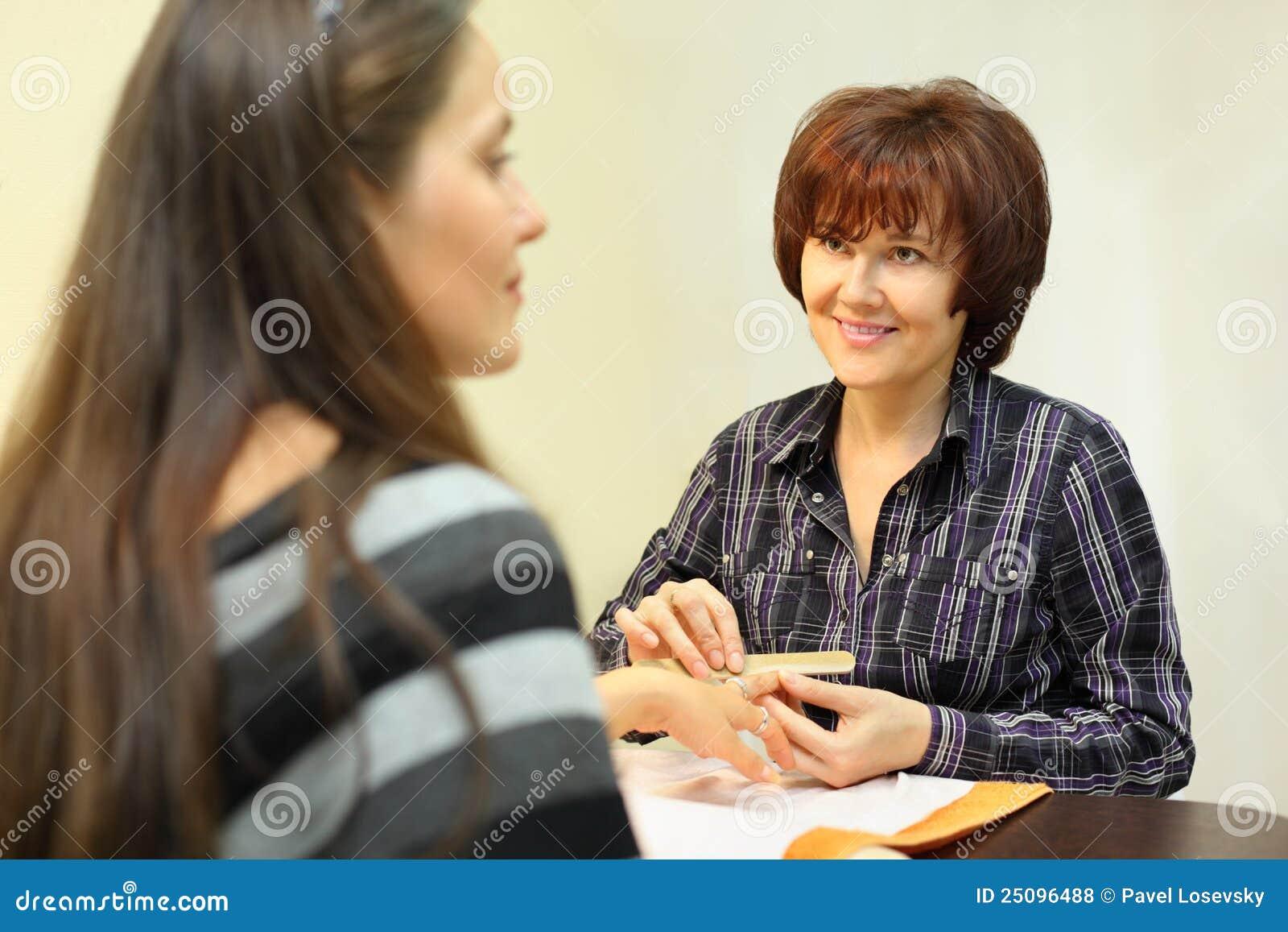 Manicuristen gör manicuren vid nailfile för kvinna