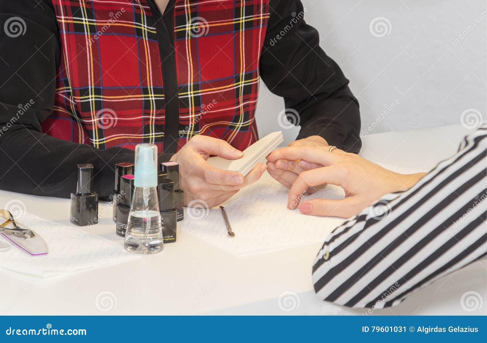 Manicuro que faz o tratamento de mãos no salão de beleza