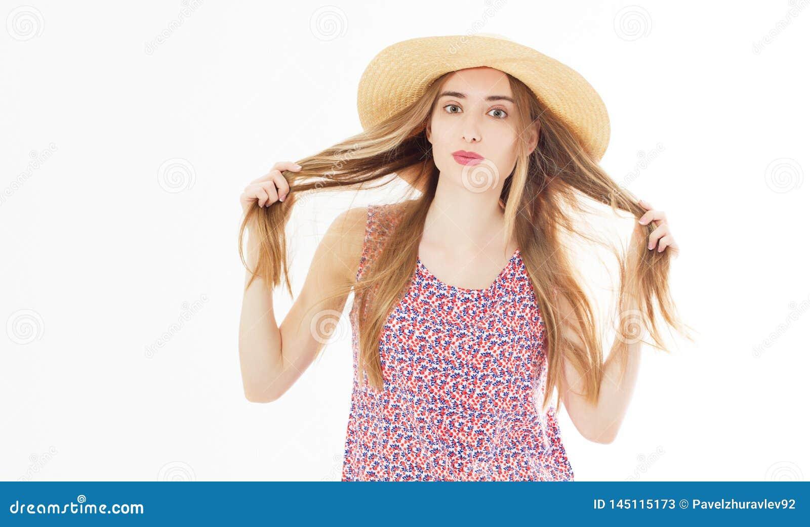 Manier en levensstijlconcept - mooie vrouw die in hoed haar haar houden die curles van zomer genieten die in openlucht op wit wor