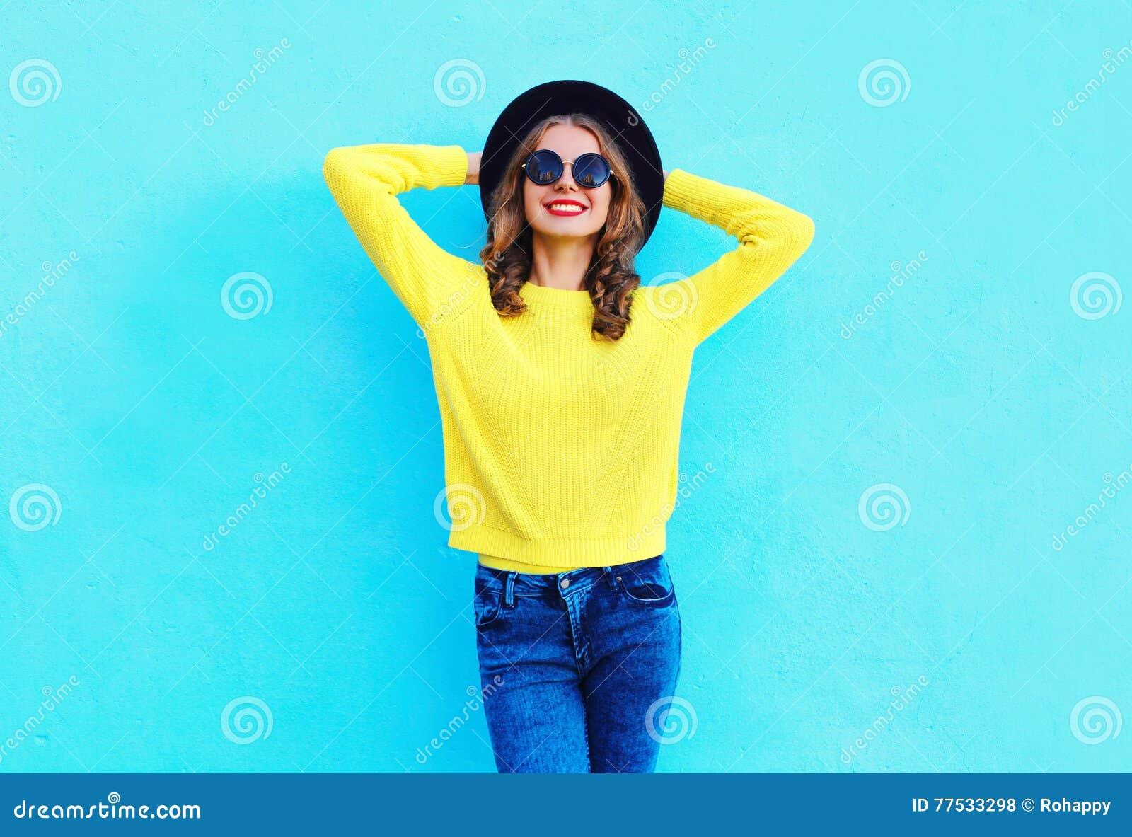 Manier gelukkige mooie glimlachende vrouw die een zwarte hoed en een gele gebreide sweater over kleurrijk blauw dragen