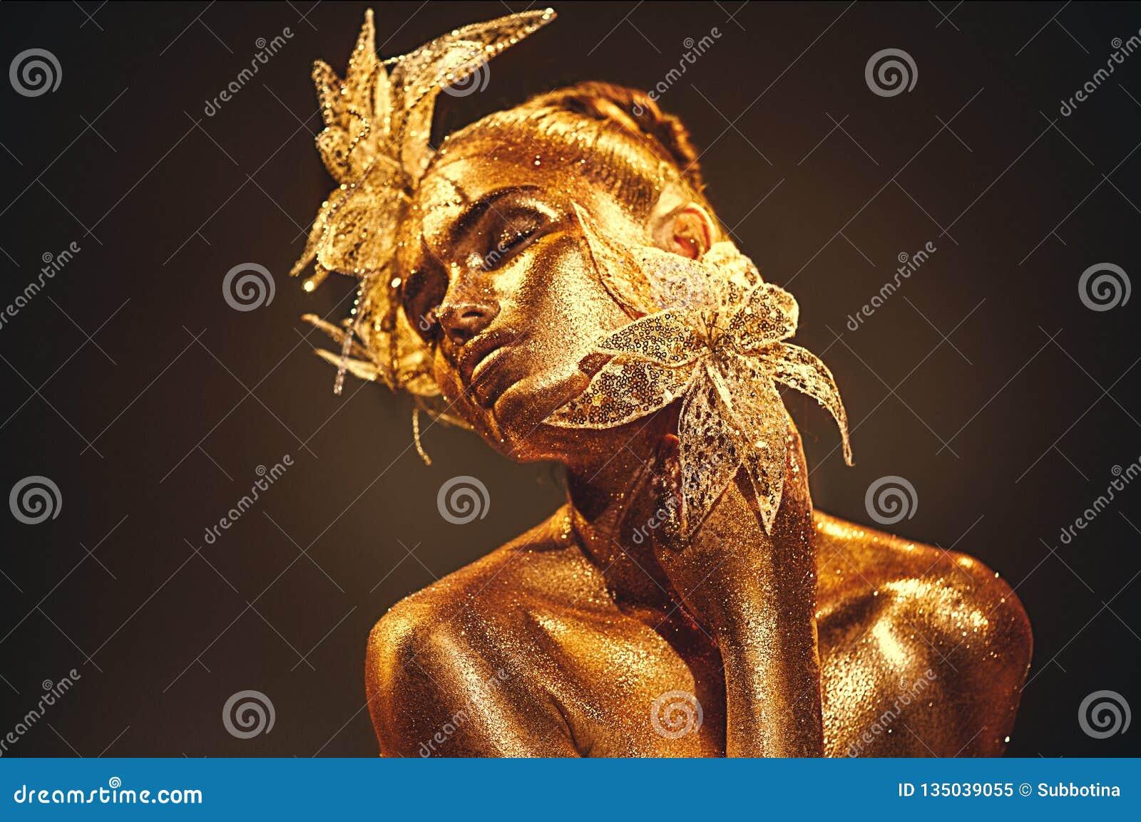 Manier gouden modelvrouw met heldere gouden fonkelingen bij huid het stellen, fantasiebloem Portret van mooi meisje met het gloei