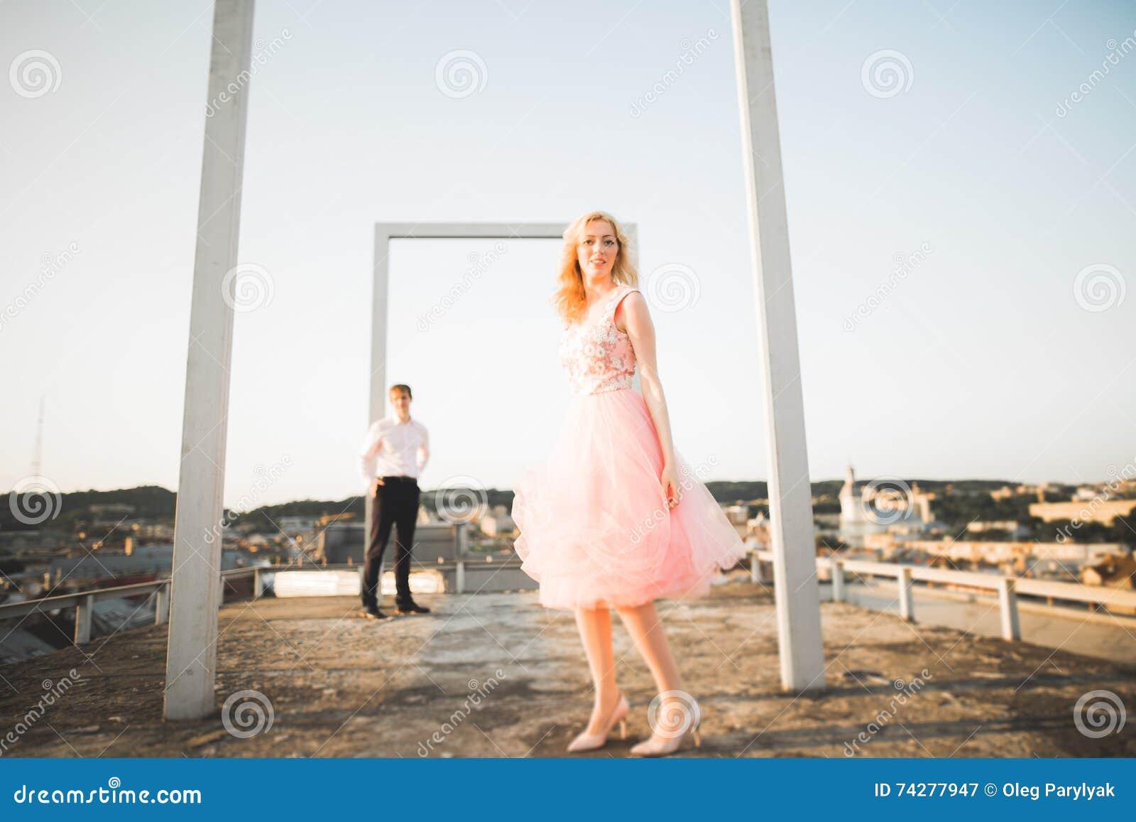 Manier het mooie mooie paar stellen op dak met stadsachtergrond Jonge mens en sensueel blonde openlucht levensstijl