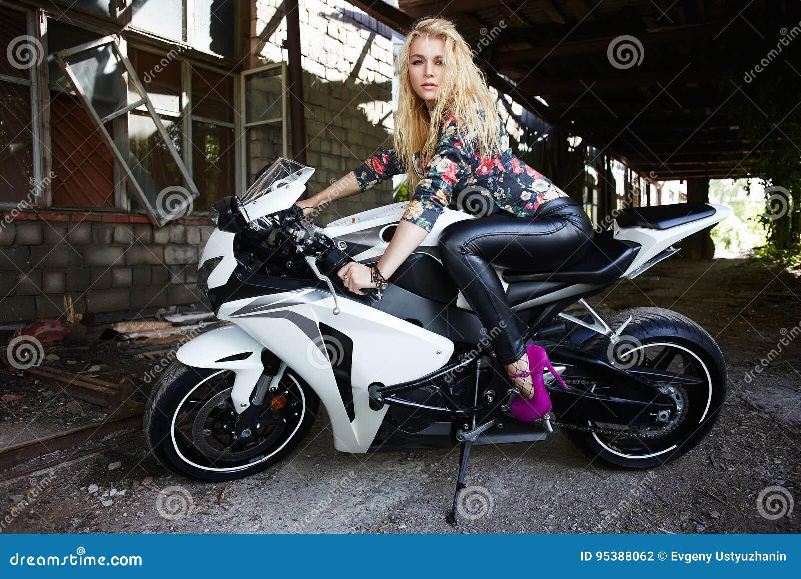 Manier jonge blonde vrouw op een sportmotorfiets
