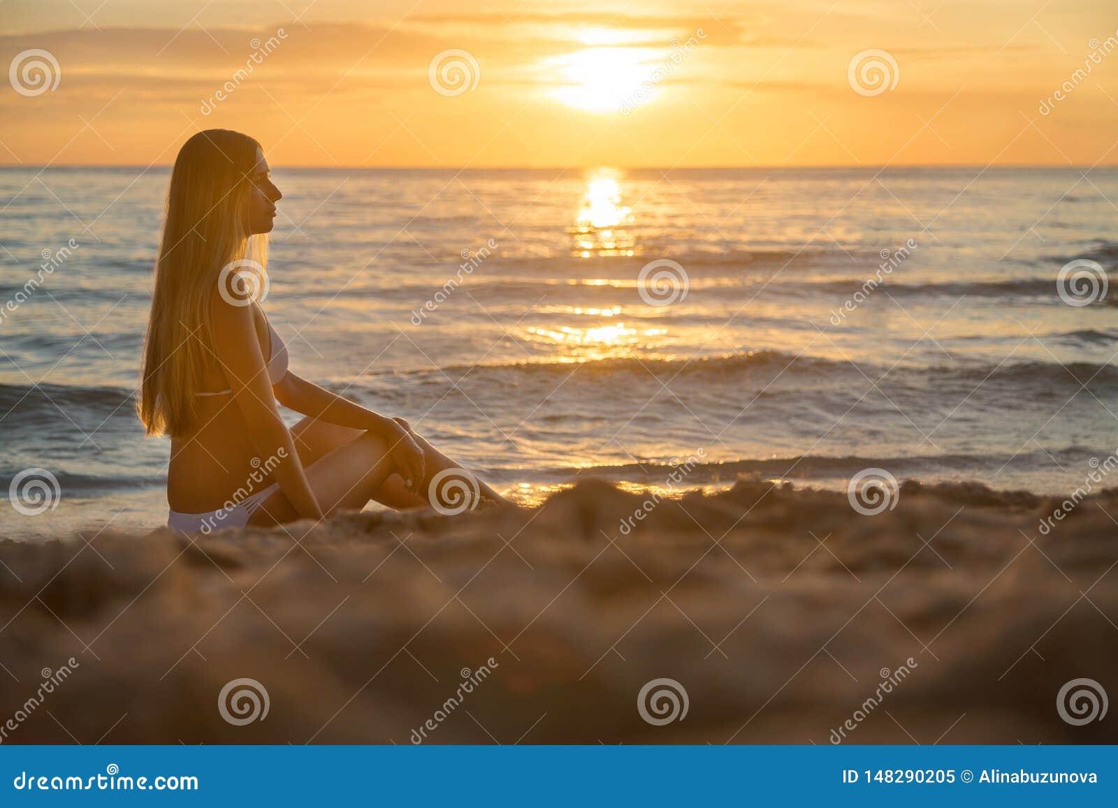 Manier openluchtfoto van sexy mooi meisje met blondehaar in het elegante witte bikini ontspannen op zonsondergangstrand