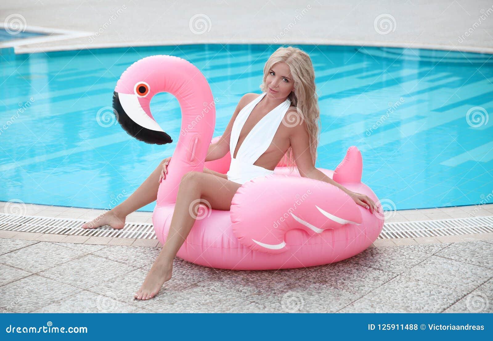 Manier sexy blonde modelvrouw in het witte bikini stellen op Roze binnen