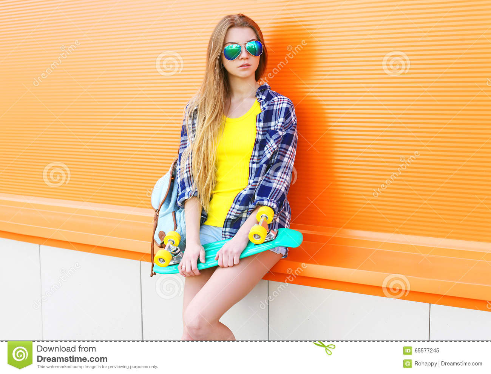Manier vrij het koele meisje dragen zonnebril met skateboard over kleurrijk