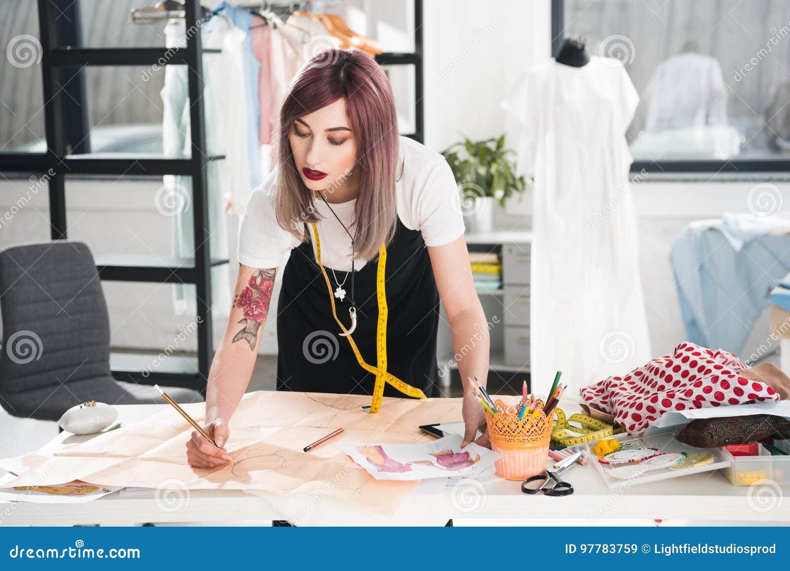 Manierontwerper die aan schets in de studio van het kledingsontwerp werken