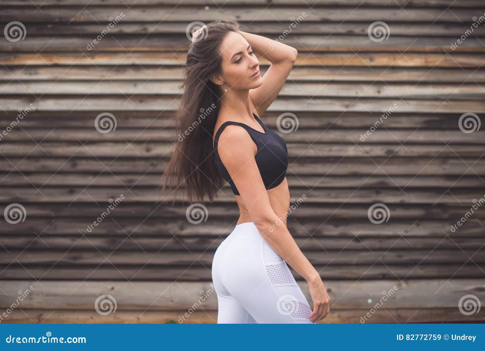 Manierportret van een jong atletisch geschikt meisje in sportkleding in openlucht Vrouw met het perfecte concept van de lichaamsg