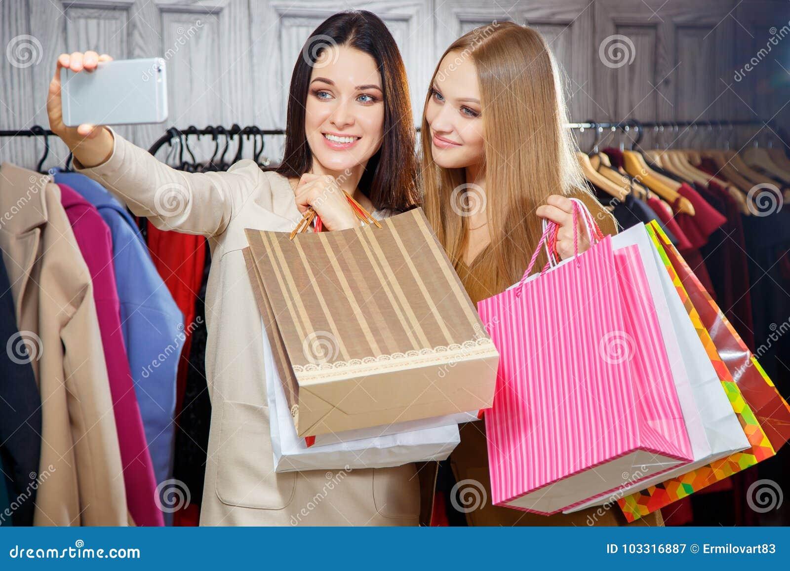 Manierportret van twee jonge mooie vrouwenvrienden in winkelcomplex met heel wat het winkelen zakken Het maken selfie
