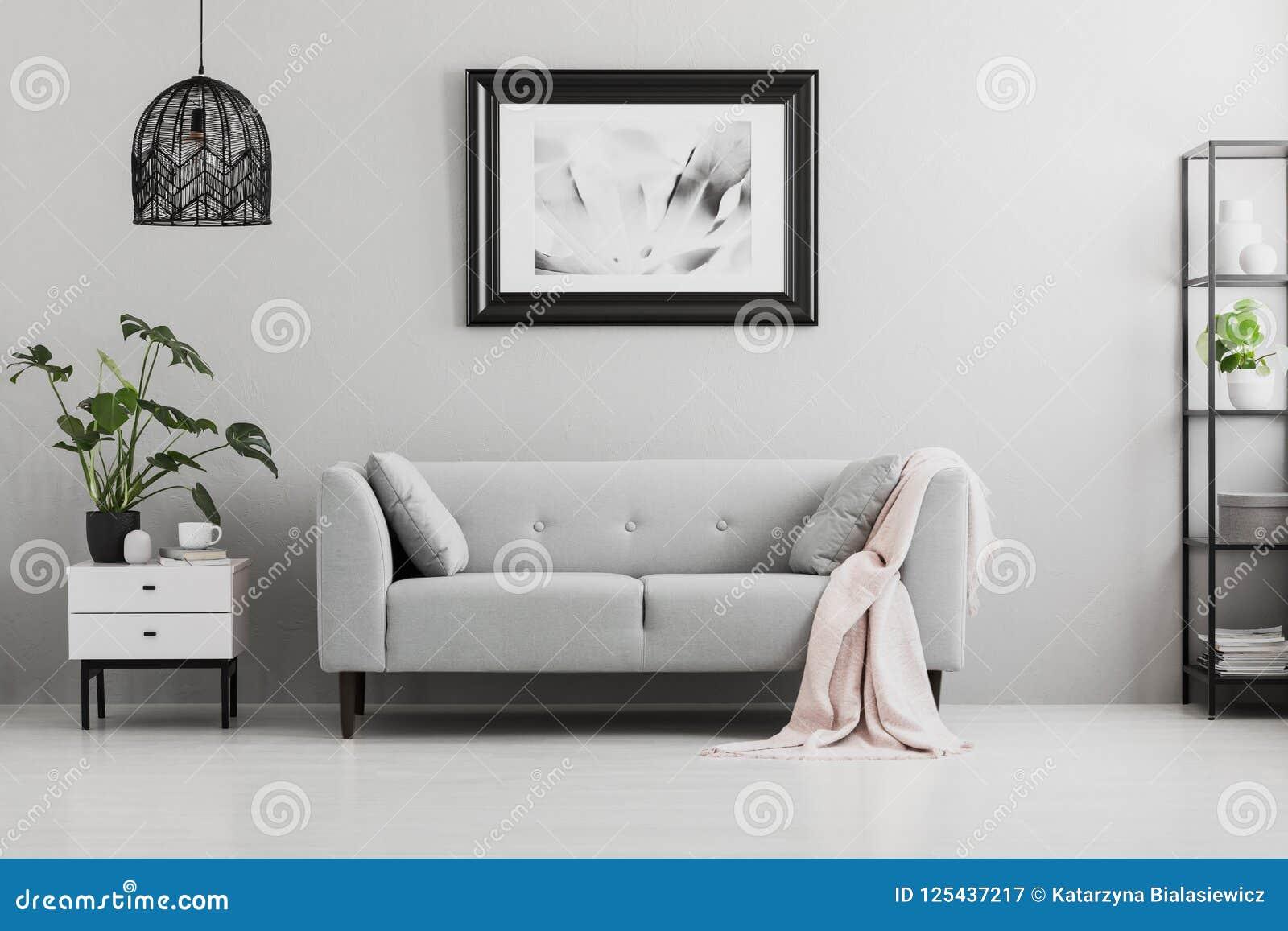Manifesto sopra il sofà grigio con la coperta rosa nell interno del salone