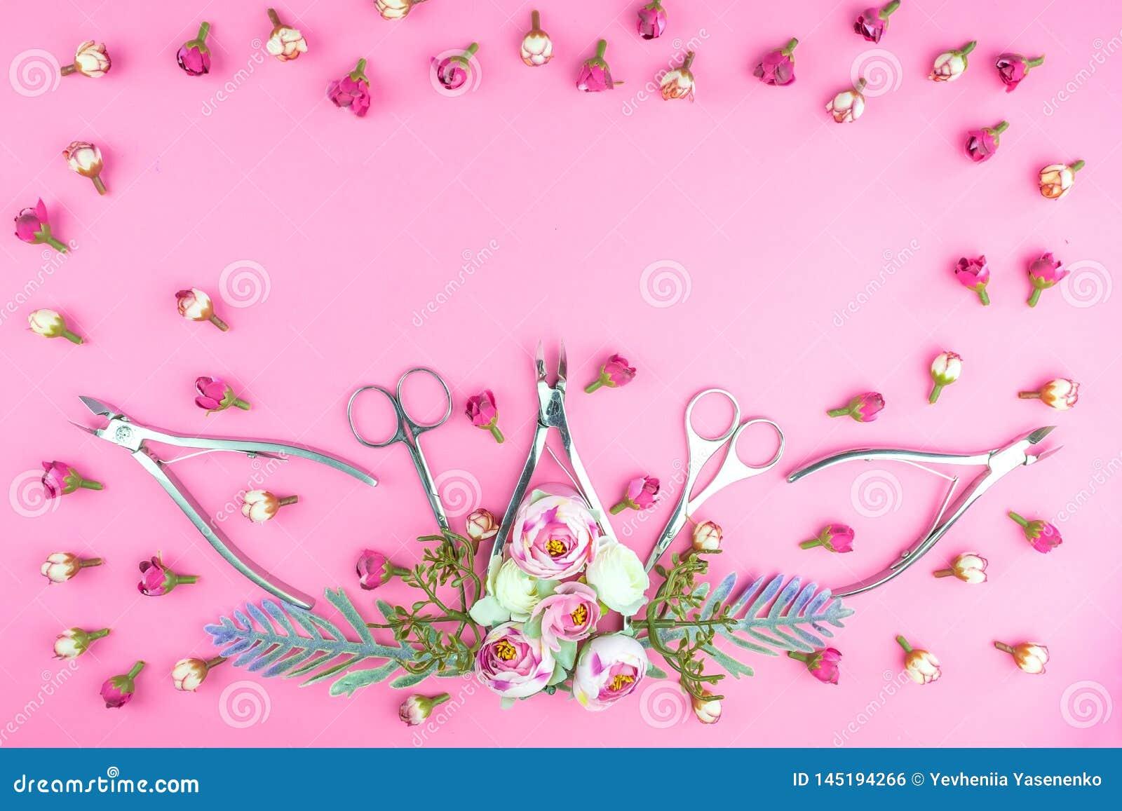 Manik?rewerkzeuge auf einem rosa Hintergrund verziert mit Blumen