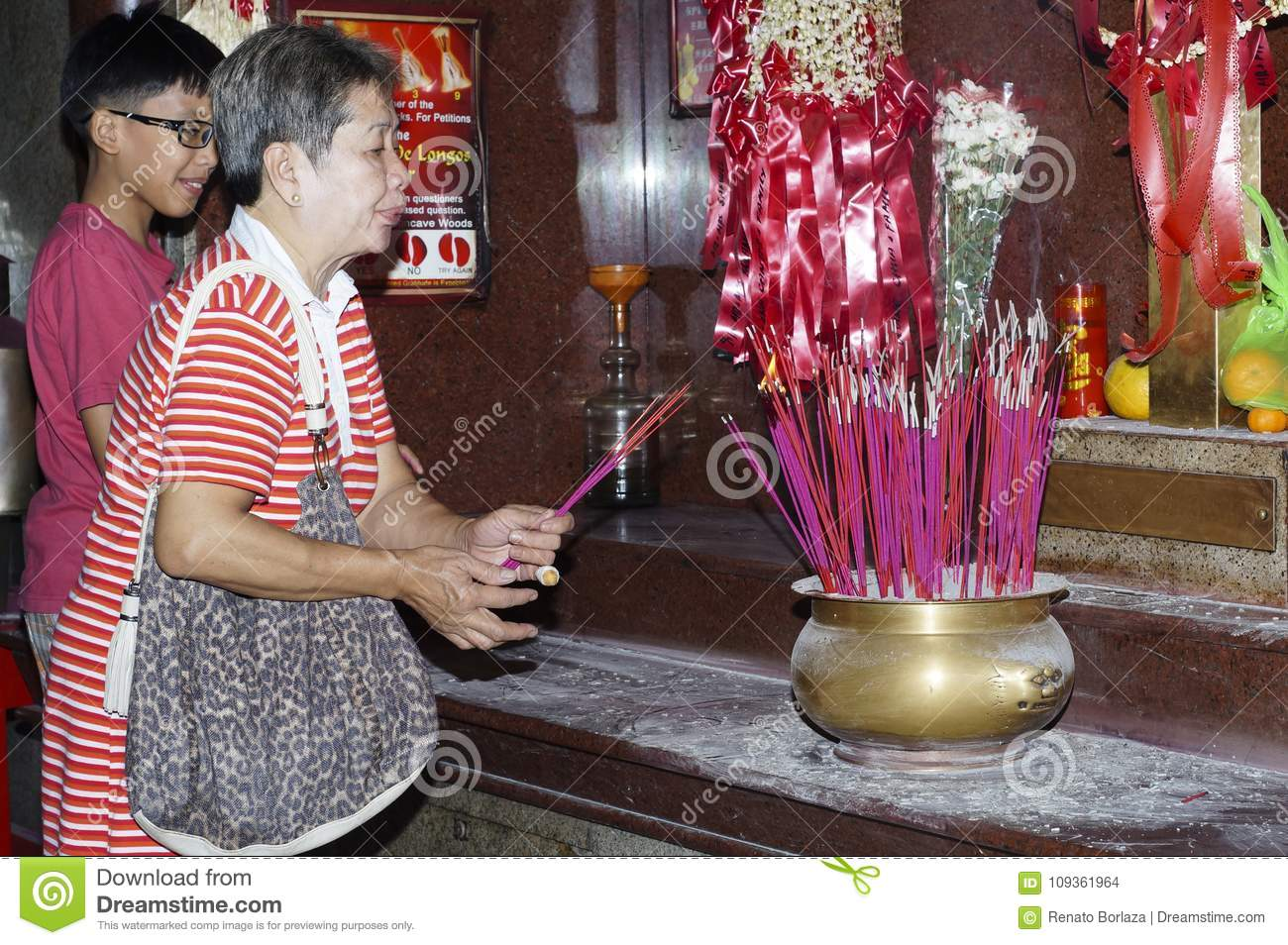 Woman light candle and jots stick to pray for departed relatives in Chinese temple in Manila