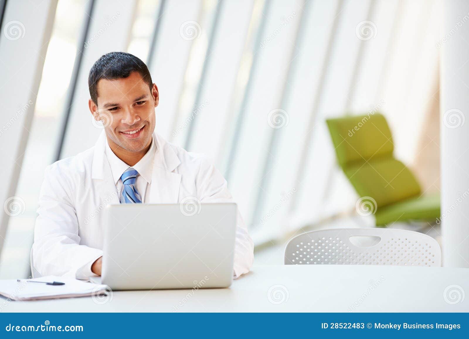 Manipulera genom att använda bärbar datorsammanträde på skrivbordet i modernt sjukhus
