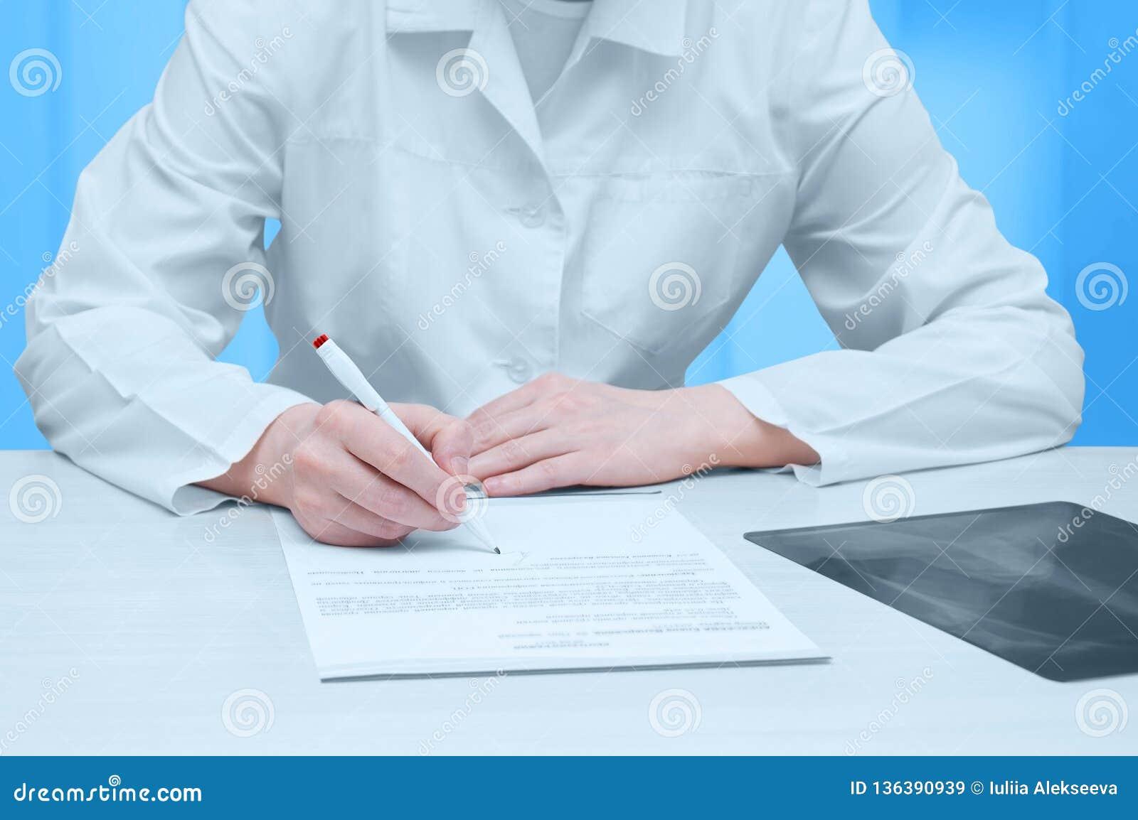Manipulera i ett vitt lag på tabellen och undertecknar en röntgenstråleexamen Närbild