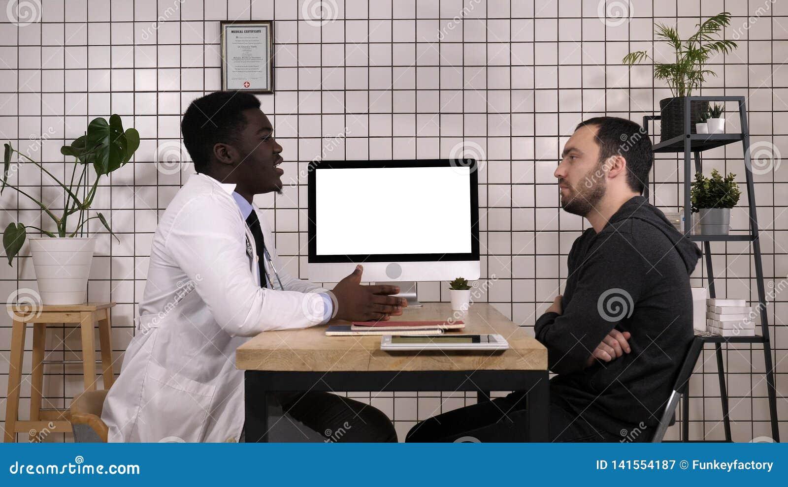 Manipulera visningsjukdomshistorier på hans dator till hans patient, honom pekar på skärmen Vit skärm