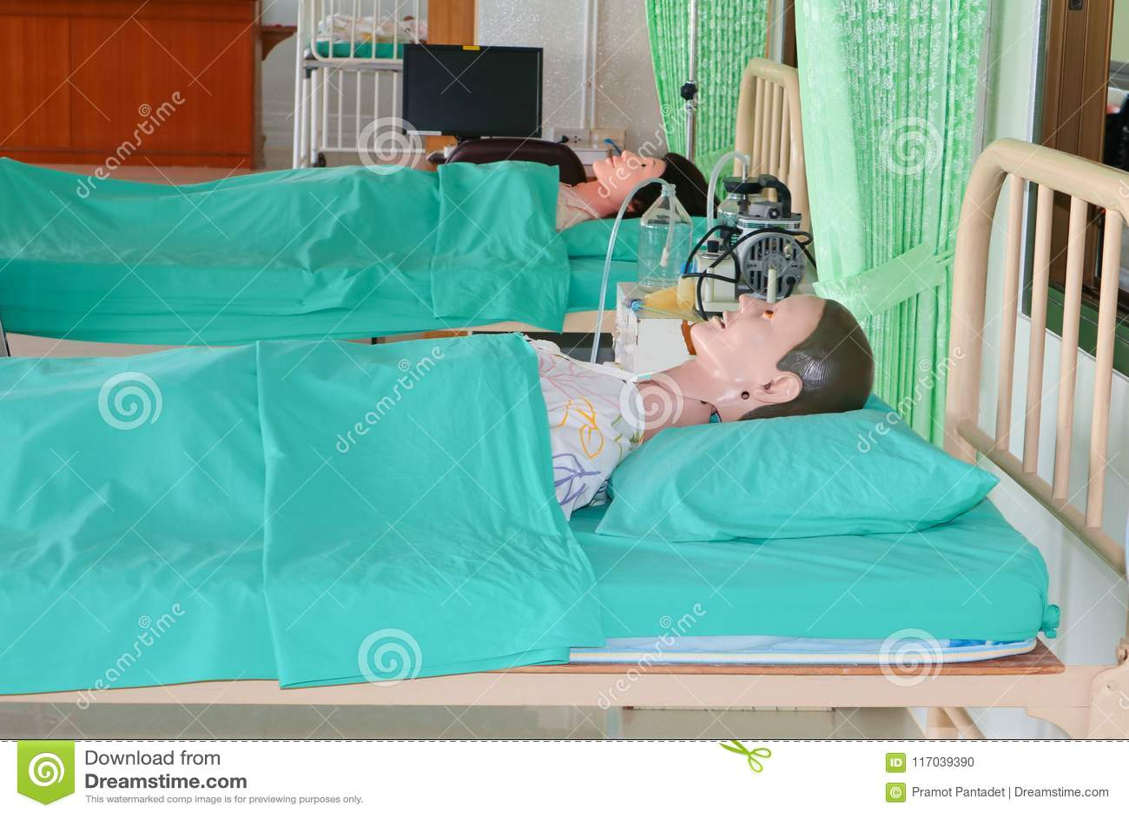 Maniquí médico en hospital, educación médica de entrenamiento del curso en cama y verde de la manta