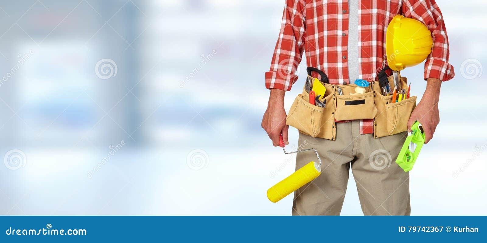Manitas del constructor con el rodillo de pintura