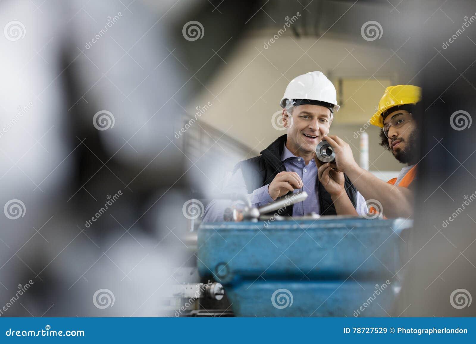 Manlig arbetsledare med undersökande metall för arbetare i bransch