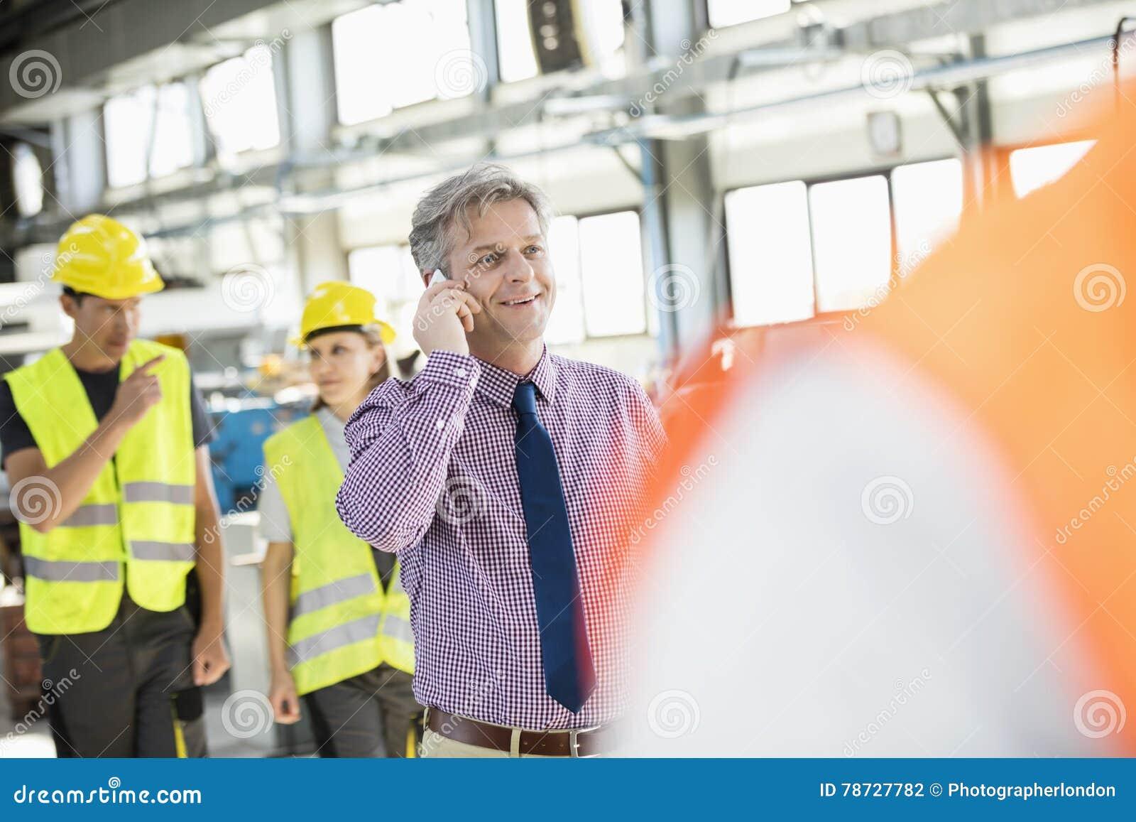 Manlig arbetsledare som talar på mobiltelefonen med arbetare i bakgrund på bransch