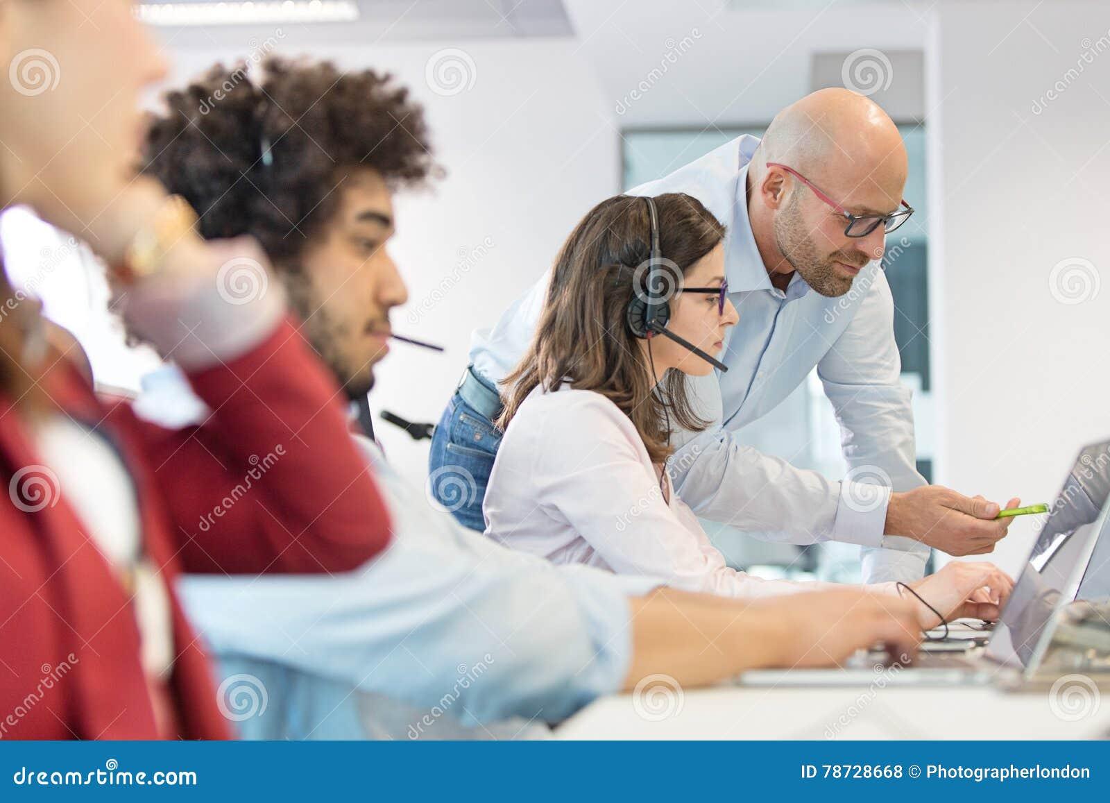Manlig chef- och kvinnligoperatör som har diskussion med kollegor i förgrund på kontoret