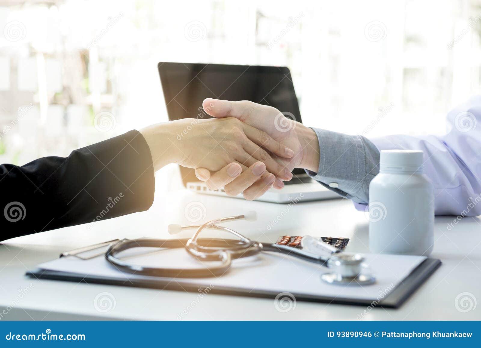Manlig doktor i det vita laget som skakar handen till den kvinnliga patienten efter s